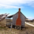 A wood poll pointing to a cottage behind it. The sky was just gorgeous.Sandy Neck\'s trail 2. Cape Cod, MA